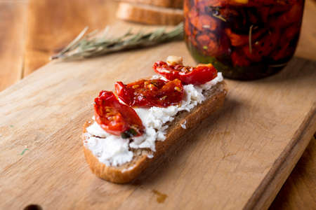 Sandwich with goat cheese, sun-dried tomatoes and thyme, served on the Board at a bright wooden surface