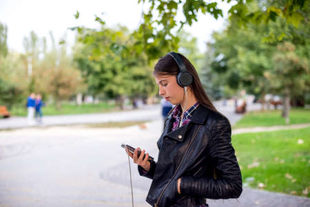 Woman listening to music. Female student girl outside in park listening to music on headphones. Happy young university student of mixed Asian and Caucasian ethnicity. Standard-Bild