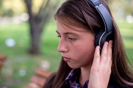 Woman listening to music. Female student girl outside in park listening to music on headphones. Happy young university student of mixed Asian and Caucasian ethnicity. Zdjęcie Seryjne - 109693580