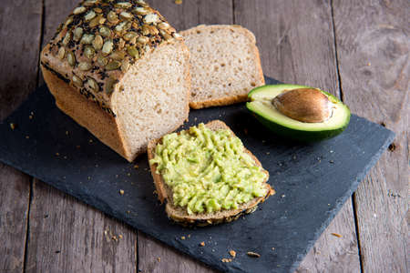 Healthy bread with fresh avocado on stone plate on wooden background. Zdjęcie Seryjne