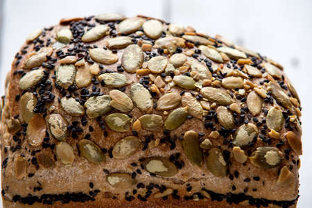 Healthy gluten free bread with seeds and nuts on wooden background
