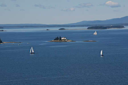 sailboats around the Pumpkin Island lighthouse just off Little Deer Isle in Maine Imagens