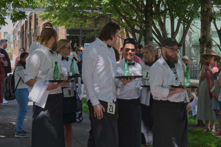PORTLAND, OREGON/USA - JULY 13, 2019 : Competitors have a moment of relaxation before the start of the Waiters' Race at the annual Bastille Day celebration sponsored by the Alliance Francaise de Portland