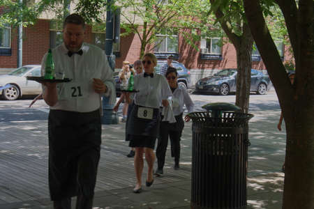 PORTLAND, OREGON/USA - JULY 13, 2019 : Competitors round a corner during the Waiters' Race at the annual Bastille Day celebration sponsored by the Alliance Francaise de Portland