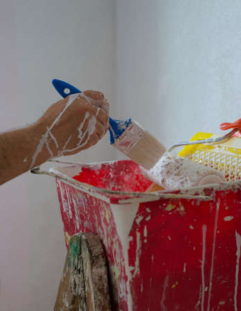 Painter man at work takes the color with paintbrush from the red bucket. Close up. The painter has his hand painted Archivio Fotografico