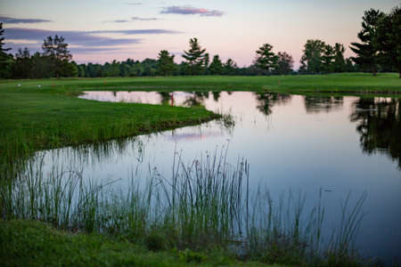 golf course hazard at sunset with pink hues in reflection of pond Stock Photo