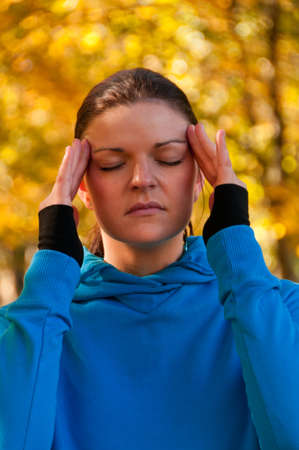 easing: A young woman massaging her temples to reduce stress.