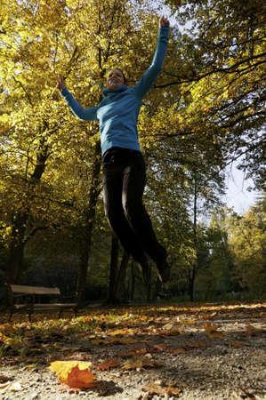 joyfully: Young girl jumping joyfully in a park