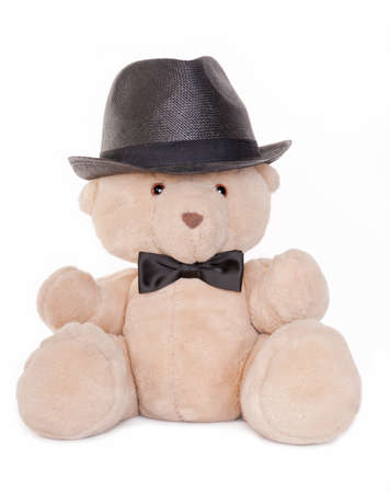 Sitting teddy bear wearing a bow tie and hat isolated on white photo