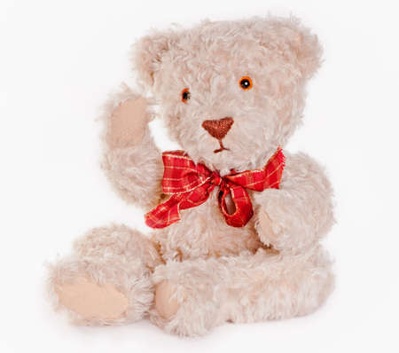 Sitting teddy bear with red bow saying hi