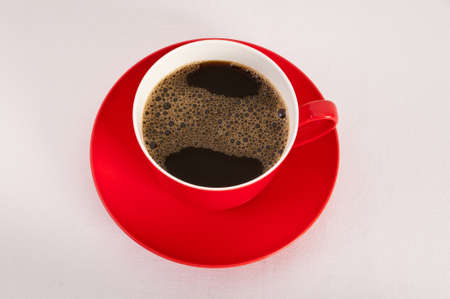 Red cup and saucer filled with black coffee on white background Stock Photo - 12635223
