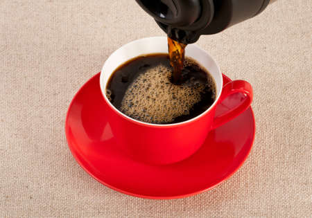 expresso: Black expresso from a coffee pot is being poured into a red coffee cup.