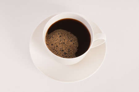 White cup filled with black coffee on white background
