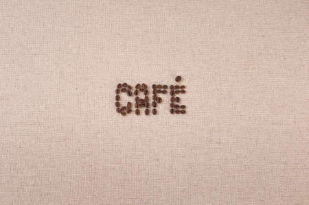 Fresh coffee beans forming the word cafe on canvas