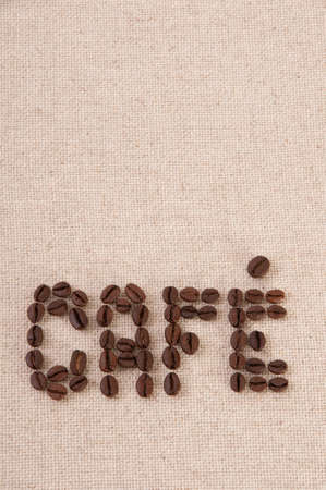Roasted coffee beans forming the word cafe on canvas photo