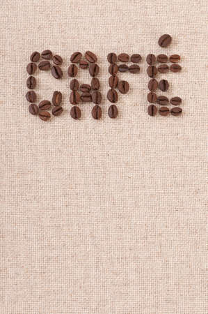 The word cafe written with coffee beans on canvas photo