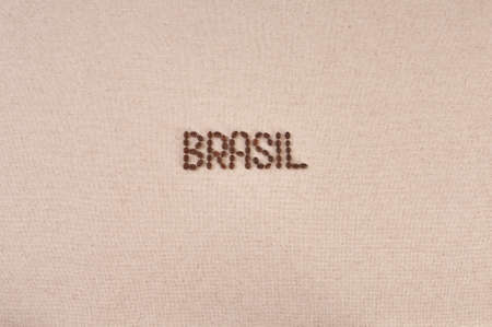 Brasil written with coffee beans in the center of a burlap background photo