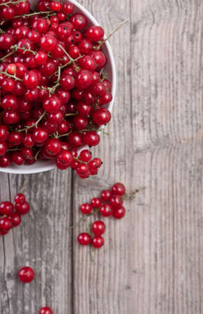 A bowl of fresh red currants on a wooden table