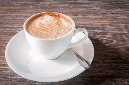 Fresh cup of coffee decorated with a milk froth leave