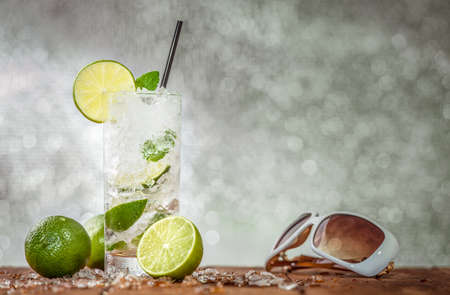 Cold drink with ice and a slice of lemon on a hot summer day party Stock Photo