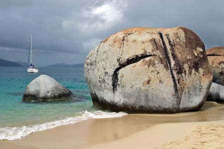 A sailboat is anchored off shore from large rock formations known as The Baths on the southern shores of Virgin Gorda in the British Virgin Islands.