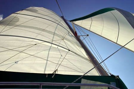 Backlit sails unfurled and taking wind with a blue sky. Stock Photo