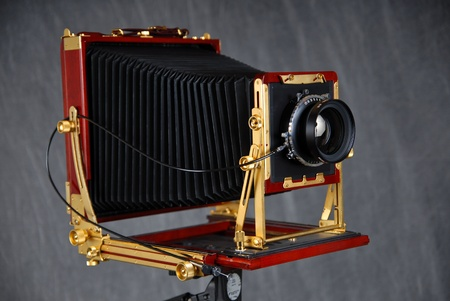 An 8x10 inch rosewood field camera with bellows, lens and cable release. Stock Photo