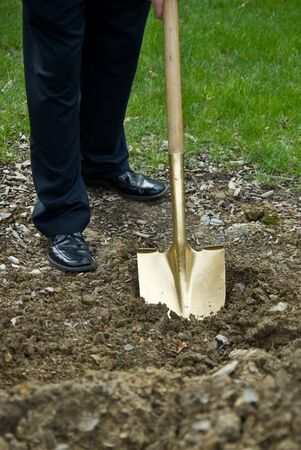 A gold shovel digs into the dirt at a groundbreaking ceremony