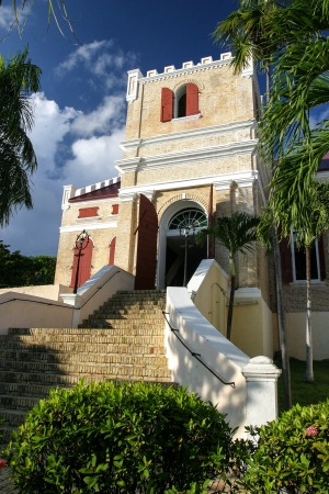 Historic Lutheran church in Charlotte Amalie on the U S  Virgin Island of St  Thomas is framed by tropical plants and blue skies