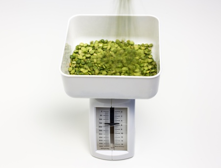 Split peas being pourned into the bin of a kitchen scale