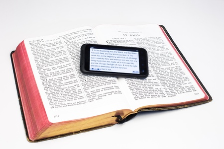 A smartphone rests on a worn Bible - both displaying the first verses of the the Gospel According to Johnl Stock Photo - 14413699