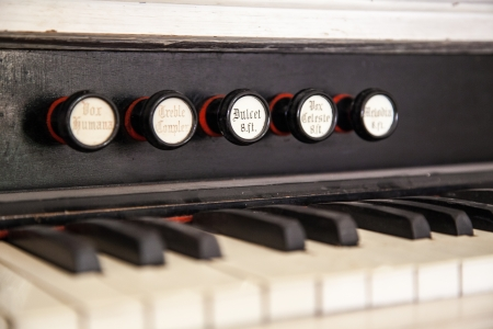 congregational: Closeup of an antique pump organ with its stops and keys