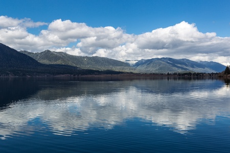 The surronding hills reflect in the calm waters of Lake Quinault in the Olympic National Forest, Washington Stock Photo