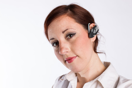 earpiece: Redheaded Woman With Bluetooth Earpiece