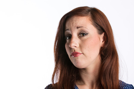 A young woman with red hair gives a sideways glance