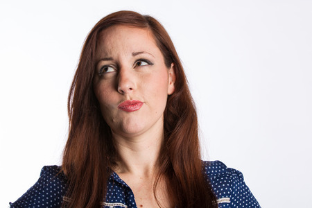 A young woman with red hair looks sideways with a puzzled look on her face
