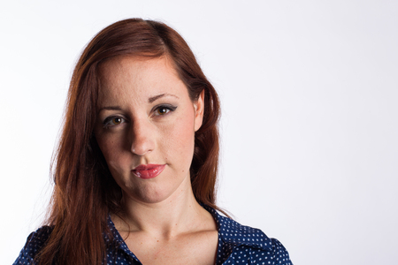 A young woman with red hair and a thoughtful look on her face  Stock Photo