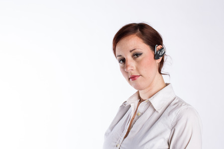 A young business woman with red hair and a serious look wears a bluetooth headset