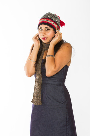 An Indian woman in a blue dress poses in front of a white background wearing a scarf and pulling down a stocking cap  Stock Photo