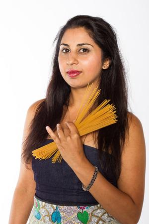 かなりインド女性は彼女の胴体の前に調理スパゲティの一握りを保持します。 写真素材