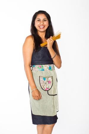 青いドレスとエプロンの笑顔のインドの女性は、彼女の胴体の前に調理スパゲティの一握りを保持しています。