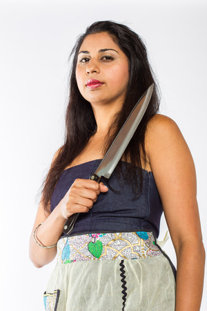 Low angle view of an Indian woman wearing a blue dress and apron with a serious look on her face holds a knife acros her body