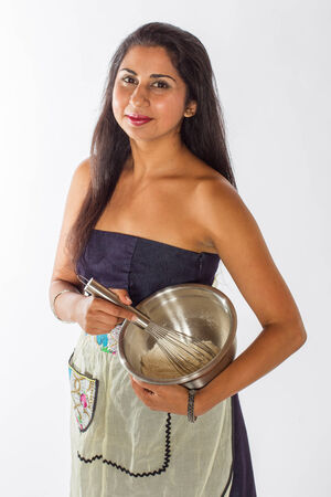 A pretty Indian woman in a blue dress and apron mixes cake ingredients in a silver bowl with a whisk  Stock Photo