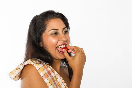 A smiling Indian woman eats a cherry tomato  Stock Photo