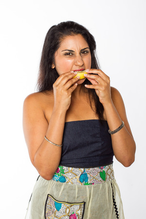 An Indian woman in a blue dress and apron grimmaces as she eats a freshly cut lemon  Stock Photo