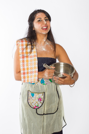 A pretty female Indian chef with flour on her face and torso with a mixing bowl and whisk at her side  Stock Photo