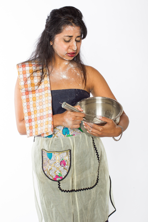 A distressed looking female Indian chef with flour on her face and torso with a mixing bowl and whisk at her side