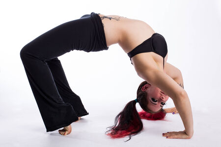 A young punk woman with dyed red hair in the upward bow, full wheel or urdhva dhanurasana yoga pose