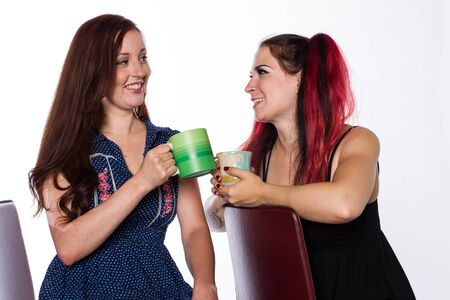 Two young women, one with red hair and one with a tattoo and dyed red hair, share conversation over coffee