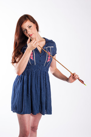 A red haired woman with a seductive look on her face checks the tip of an arrow
